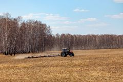 Red tractor with a trailed plow for mowing and weeding fields for the agro-industry of yellow color under the blue sky, a clear. Spring day. Preparation for royalty free stock image