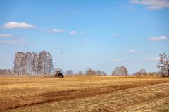 Red tractor with a trailed plow for mowing and weeding fields for the agro-industry of yellow color under the blue sky, a clear. Spring day. Preparation for royalty free stock photography