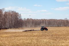 Red tractor with a trailed plow for mowing and weeding fields for the agro-industry of yellow color under the blue sky, a clear. Spring day. Preparation for royalty free stock images