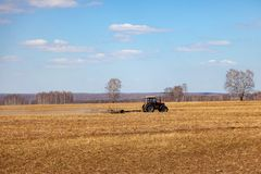 Red tractor with a trailed plow for mowing and weeding fields for the agro-industry of yellow color under the blue sky, a clear. Spring day. Preparation for stock photo