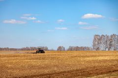 Red tractor with a trailed plow for mowing and weeding fields for the agro-industry of yellow color under the blue sky, a clear. Spring day. Preparation for royalty free stock photos