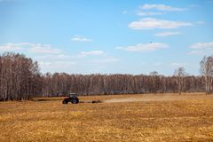 Red tractor with a trailed plow for mowing and weeding fields for the agro-industry of yellow color under the blue sky, a clear. Spring day. Preparation for stock photography