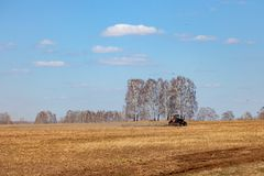 Red tractor with a trailed plow for mowing and weeding fields for the agro-industry of yellow color under the blue sky, a clear. Spring day. Preparation for stock image