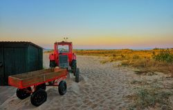 Red tractor with trailer on the beach in Ahlbeck. Germany
