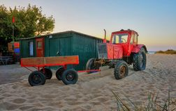 Red tractor with trailer at the fisherman house on the beach in Ahlbeck. Germany