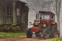 Red tractor by the wooden building Royalty Free Stock Photography
