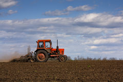 Red tractor working in a field Stock Image