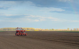 Red tractor working on thre agricultural field Royalty Free Stock Photography