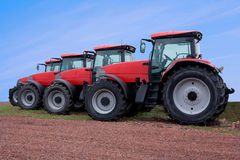 Red Tractors. Red farming tractors parked near a field, on the backdrop of clear blue sky Stock Image