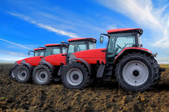 Red tractors on field. Row of red tractors on field in countryside under cloudscape Stock Photography