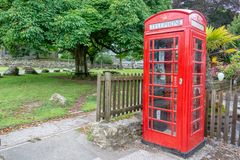 Red traditional english Phone booth in Widecombe in the Moor, Devon UK. Red traditional english Phone booth in Widecombe in the Moor, Devon, UK royalty free stock images