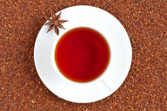 Red traditional rooibos tea full of antioxidant in. Red traditional organic rooibos tea full of antioxidant in white cup on raw rooibos tea background Royalty Free Stock Photography