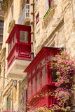 Red traditional wooden Maltese balconies in Valletta. Red wooden balconies against warm sunlit limestone walls, with a colorful vine plant growing, Valletta Stock Photo