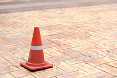 Red traffic cone on tiled rock pavement Royalty Free Stock Photos