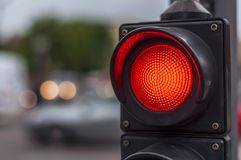 Red traffic light in the city street. Red traffic light with blurry background in the city street close Royalty Free Stock Photo