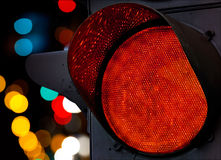 Red traffic light with colorful unfocused lights Stock Photos