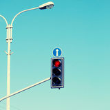 Red traffic light. S with arrow against blue sky background. Square toned image, instagram effect Stock Image
