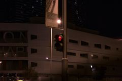 Red traffic light at night, for pedestrians on the street - warning sign not to cross the road royalty free stock image