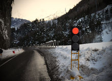 Red traffic light for snow or bad weather. Mountains: red traffic light for avalanche, snowy weather, ice on street Royalty Free Stock Photography