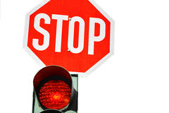 Red traffic light and a stop sign. Stock Image