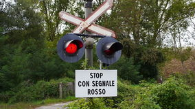Red traffic light at train crossing. In Italian town with warning sign stock video