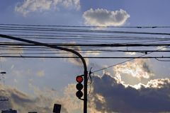 Red traffic light under sky with loaded clouds Stock Image