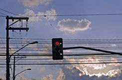 Red traffic light under sky with loaded clouds Royalty Free Stock Photos