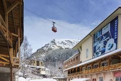 The Red trailer of the old cable car moves over the hotels of the resort village. Snowy frosty day royalty free stock photo