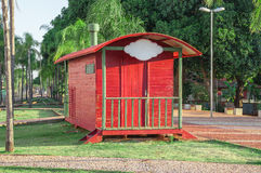Red trailer through the park with old railway track, some benches and many trees and green nature around. Plate to put your brand. Royalty Free Stock Images
