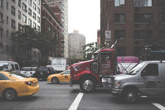Red Trailer Truck Beside Gray Van at the City Royalty Free Stock Photo