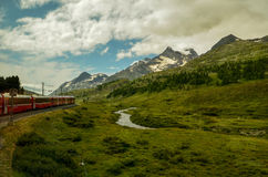 Red train through the alps in Switzerland. Photo shows red panoramic train through the alps in Switzerland. Fields of grass, trees and high mountains Stock Image