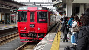 Red train approaching train station. In Japan. People are waiting to get into train. Some are taking photographs royalty free stock photo