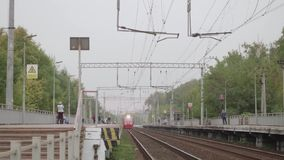 Red train arrives at station. On cloudy autumn day stock video footage