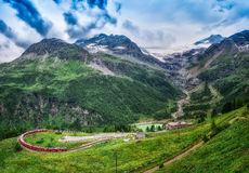 Red train Bernina Express to the passage in the mountains. Royalty Free Stock Photo