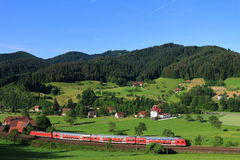 Red train in Black Forest landscape. The characteristic landscape of the Black Forest in Germany at a sunny day in summer with a red train passing by Stock Photo