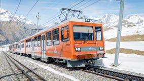 Red train climbing up to Gornergrat station on Zermatt, Switzerland. The Gornergrat rack rail. ZERMATT, SWITZERLAND - May 16. 2017: Red train climbing up to stock image