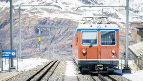 Red train climbing up to Gornergrat station on Zermatt, Switzerland. The Gornergrat rack rail. ZERMATT, SWITZERLAND - May 16. 2017: Red train climbing up to stock photos