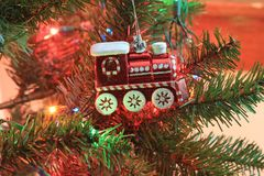 Red Train Closeup on a Christmas Tree. A RED TRAIN shot closeup on a Christmas Tree with Christmas lights that are bright and colorful on the Christmas season Stock Image