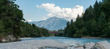 Free Red Train Crosses A Bridge Over The River Rhine In The Swiss Alps Stock Photography - 154689252