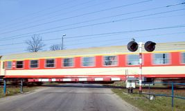 Red train crossing. A train crossing, blur motion, red car, some cables in the blue sky, warning traffic lights Royalty Free Stock Images