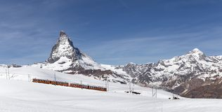 Red Train in front of Matterhorn. Zermatt, Switzerland - April 12, 2017: A red train in front of the snowy Matterhorn mountain stock photo