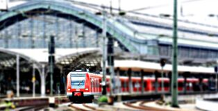 Red Train at a Green Train Station on an Overcast Day Royalty Free Stock Photo
