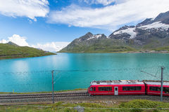 Red train in the high mountains of the Swiss Alps passes near a Stock Photography