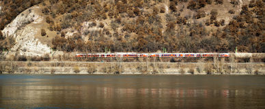 Red train is on the other side. Of the river by Danube royalty free stock photography