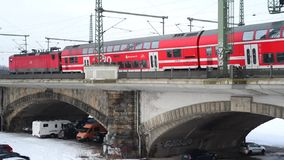 Red train passing by on a concrete bridge in urban area city on cloudy day stock footage