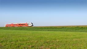 Red train passing through fields. Red and white train passing by through green fields stock footage