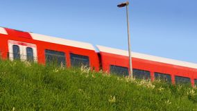 Red train passing on higher platform. Red and white diesel train passing on higher platformn stock footage