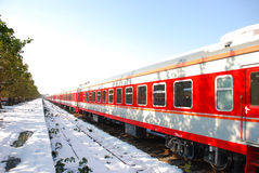 The red train on platform in winter. The red train and trees on platform with snow in winter Stock Photo