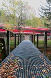 Red train quickly passing a lake with a bridge in Germany stock photography