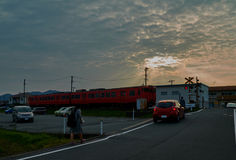 The red train running under the sunbeam before sunset. During the train coming, the cars and people are waiting for the train pass Stock Photography